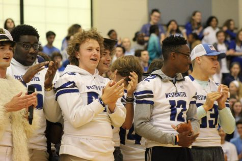 Varsity football players and cheerleaders perform a dance together at the Homecoming pep assembly.