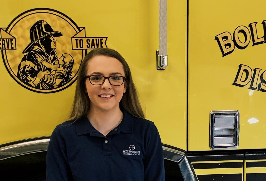 Hannah Carter stands with a firetruck from the Boles Fire Protection District.