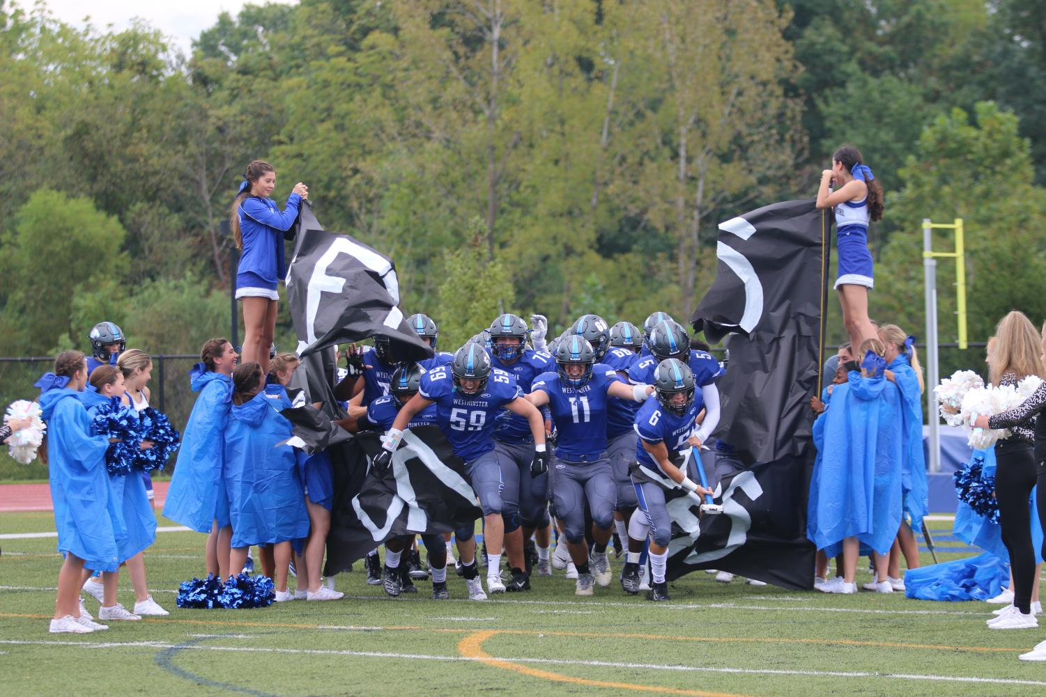 The Wildcats run out through the banner before their game against Lutheran North.