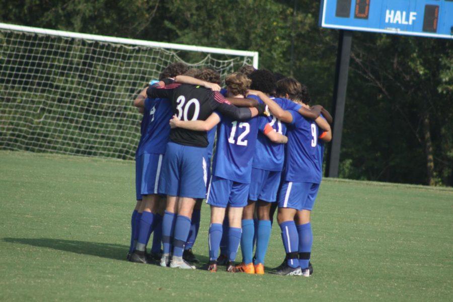 The+team+huddles+to+pray+before+the+start+of+a+regular+season+match.