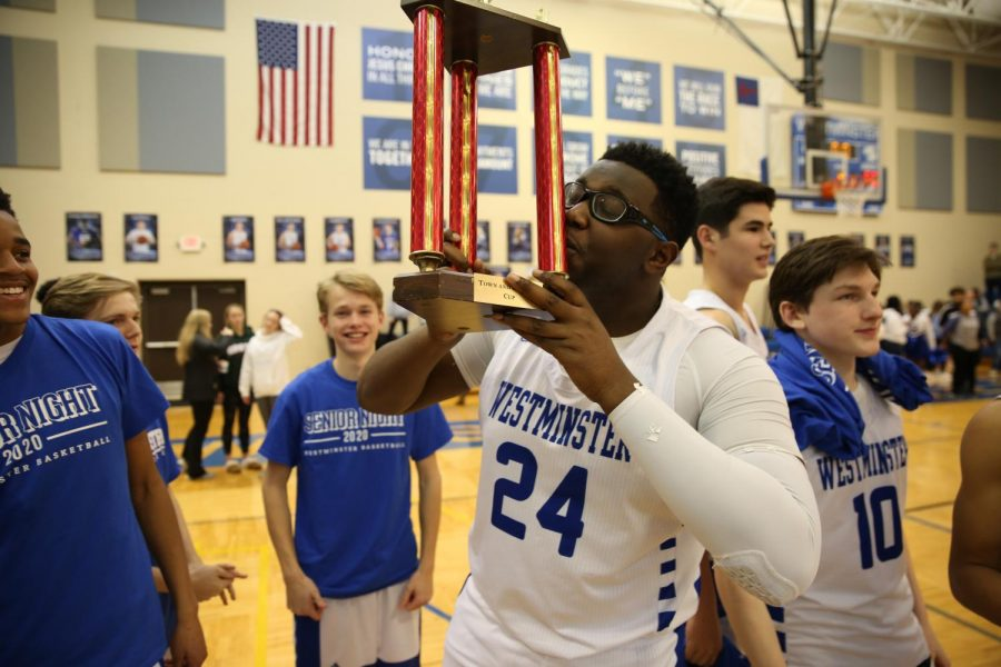 Senior Bennie Anderson kisses the Town and Country Cup. The Cup will remain at Westminster.