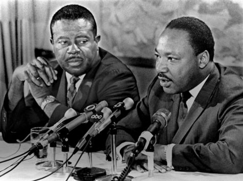 Ralph Abernathy listening to Dr. King as he gives a speech.