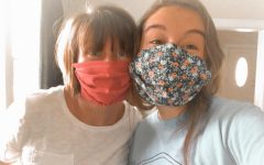 Molly poses with her mom in some of the masks that she made.
