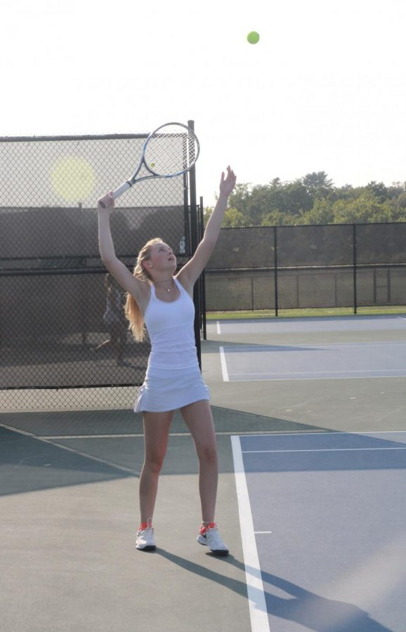 Hailey Colley tosses the ball in the air to serve.