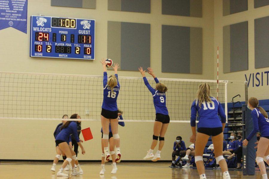 Alli Bishop, sophomore, and Emma Volding, senior, jump up for the block.
