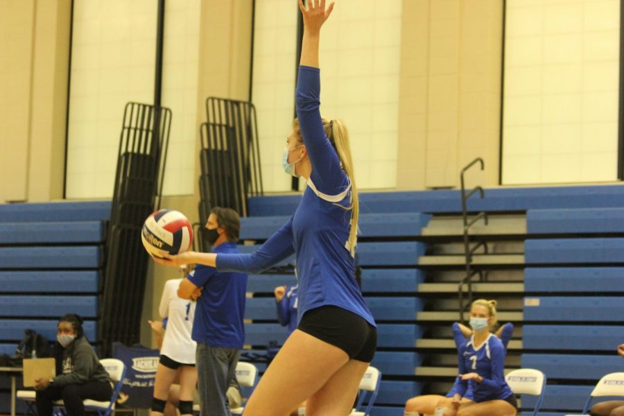Alli Bishop tosses the ball up to serve against Ladue.