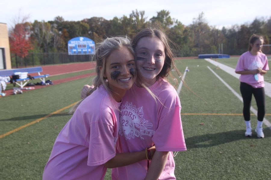 two juniors posing on the sidelines of the junior senior powderpuff game.