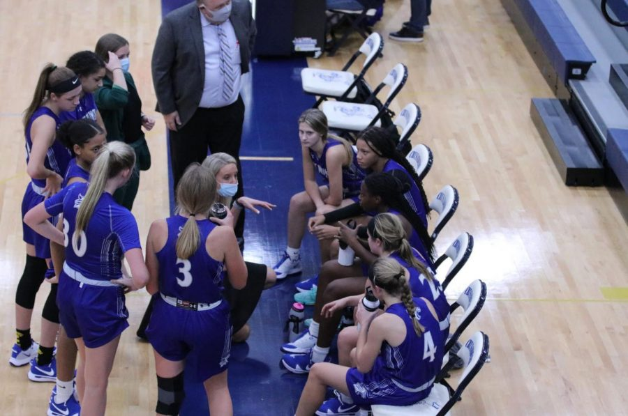 The girls regroup during a timeout in the second half.