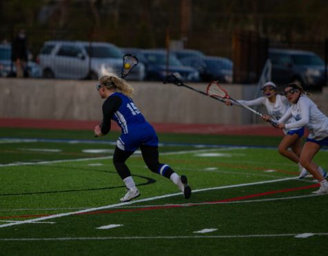 Kharis Perona runs down the field with the ball in her stick.
