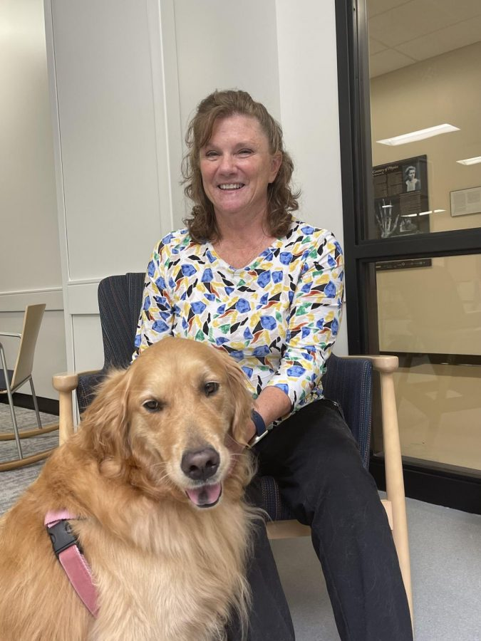 Mrs. Brown sits in the Hub while petting Millie. She enjoys having Millie back for the students.