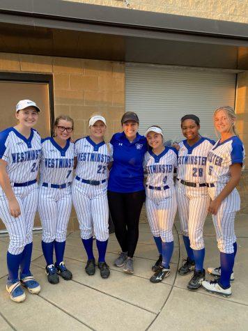 Coach Farmer smiles with the senior softball players on senior night.