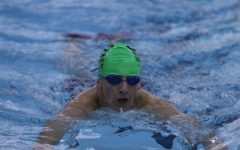 A close up with Jacob Schloss as he swims to the wall.