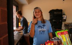 one of he food booth workers gives a thumbs up for how the carnival is going.